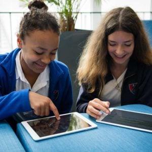 Schülerinnen arbeiten mit iPads im Unterricht