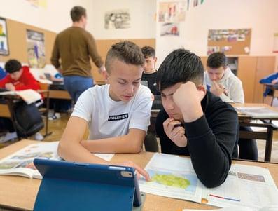 In einem gefüllten Klassenzimmer arbeiten zwei Jungs gemeinsam an einer Aufgabe aus Geografie